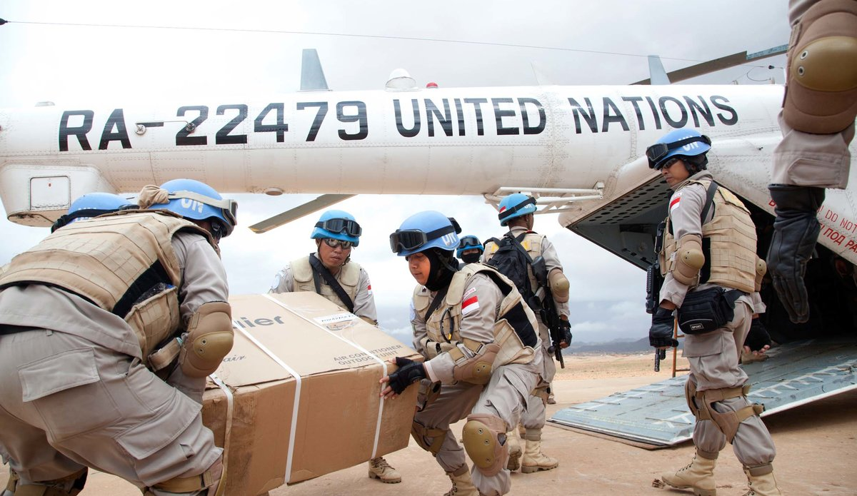 UNMIL peacekeepers offload supplies from a UN helicopter