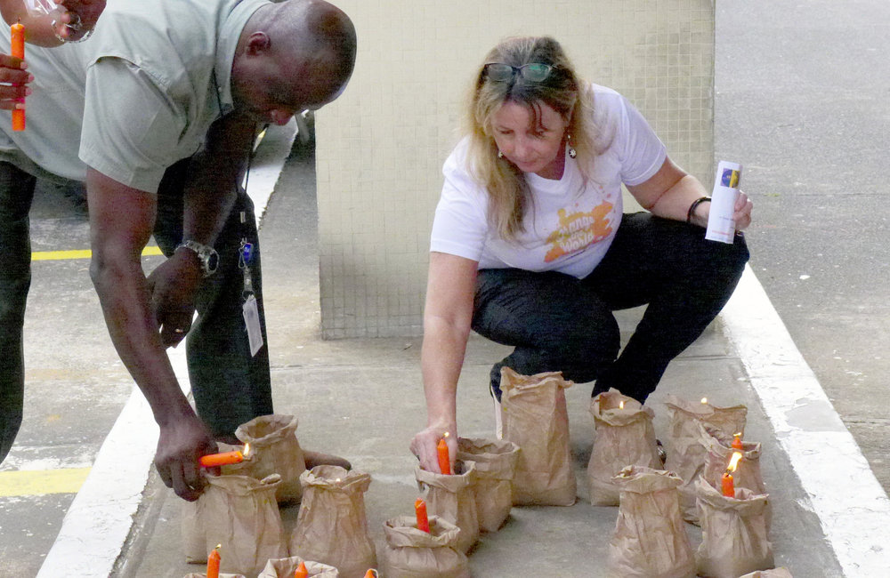 Head of PIO, Ms. Leigh Robinson lighting a candle on symbolism of 16 days of activism for no violence against women & children and Human Rights day ©UNMIL Photo: Shpend Berbatovci